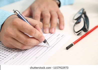 Picture of man is filling OMR sheet handing with pen.