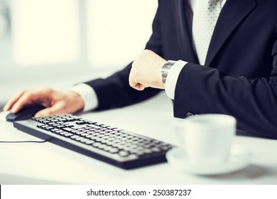 picture of man hands typing on keyboard and watching time