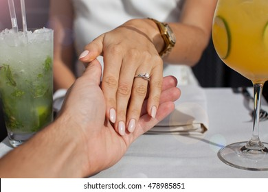 Picture of man putting beautiful engagement ring on his girlfriend hand. Proposal concept.