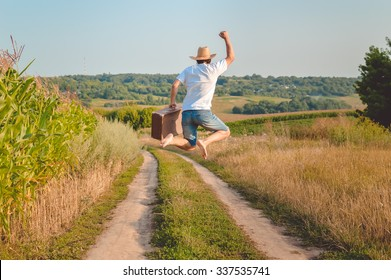 Picture of man in straw hat holding old valize and jumping on country road. Back view of excited traveler on blurred sunny outdoor background.