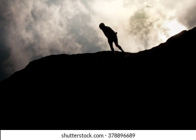 Picture of a man walking on the top of a hill. High contrast with clouds on background.