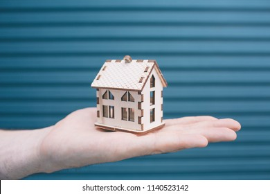 A picture of man's hand holding a small toy. It it house made from wood. It has light color. House is standing on man's hand. Isolated on striped and blue background.