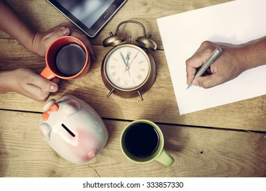Picture of man's hand writing and woman's hands holding cup of coffee beside piggy-bank and alarm-clock. Top view of  family planning some purchasing on wooden plank table background.