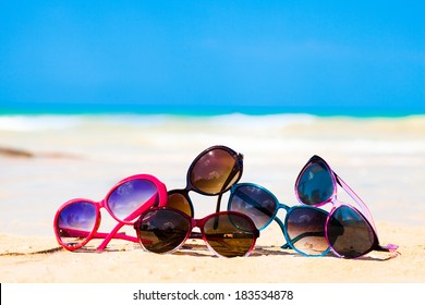 picture many sunglasses lying on tropical beach