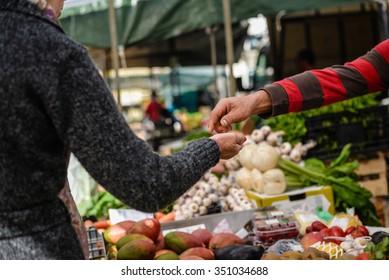 Bild des Marktplatzes mit verschiedenen Früchten. Hände des Käufers und Verkäufers auf buntem Hintergrund im Freien