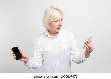 A picture of mature woman that holding two phones in her hands. She used to use the old phone. The woman doesn't know how to use the new phone. It looks quite unusual. Isolated on white background.
