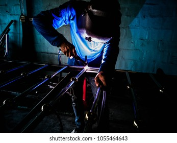 Picture of mechanic welding aluminum door with electric welding machine.