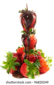A picture of melted chocolate that is poured over a tower of strawberries