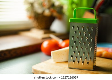 Picture of metal kitchen grater with oval holes on it on the kitchen table