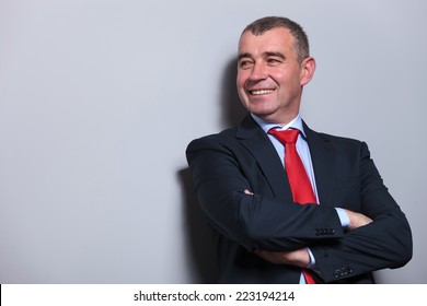 Picture of a mid aged business man leaning on grey wall with his arms crossed while looking away from the camera.