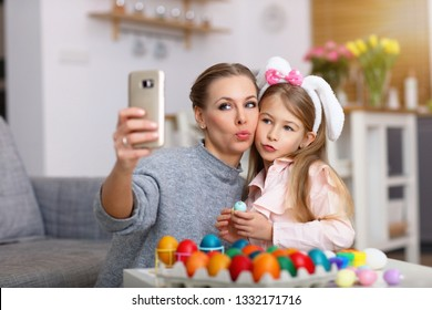 Picture of mother and daughter painting Easter eggs and taking selfie