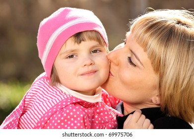 A picture of mother kissing her little girl in the park