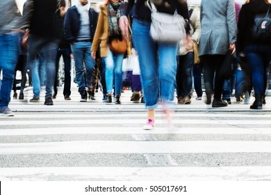 picture with motion blur of a crowd of people crossing a city street at the pedestrian crossing