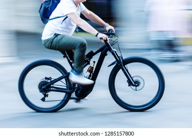 picture in motion blur of a cyclist in the city who transports a beer bottle at the bicycle