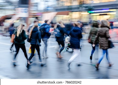 picture in motion blur of a wintry street scene in the city with people crossing a street