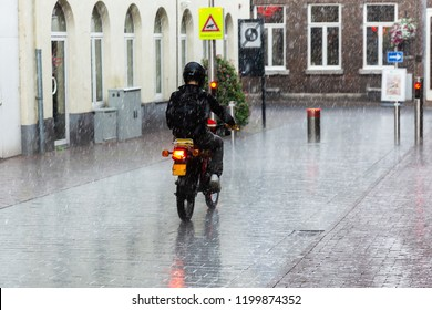 picture of a motorbike rider on the street during heavy rain