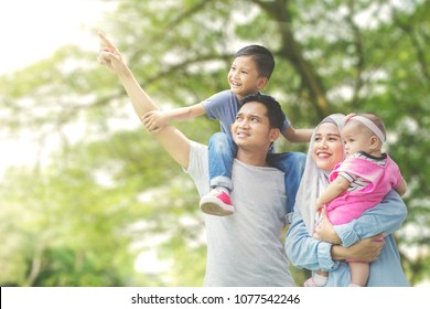 Picture of Muslim family looking at something while standing together in the park