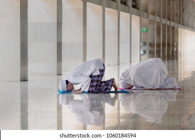 Picture of Muslim man with his wife posing prostration while doing Salat in the mosque