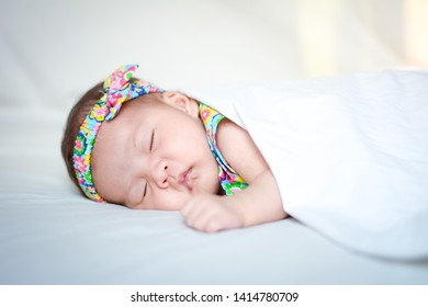 picture of a newborn baby sleeping on a white blanket