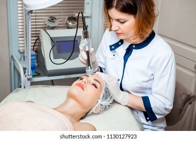 picture of nice beautician doing oxygen therapy for young woman laying down with closed eyes in a beauty salon