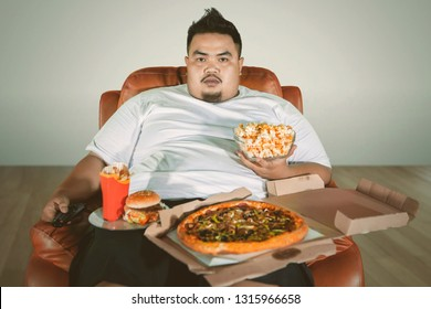 Picture of an obese man watching TV on the sofa while eating junk foods at home