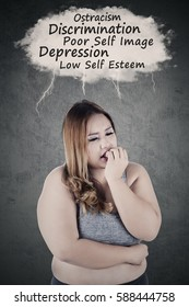 Picture of obese woman looks depressed, thinking her problems while biting nails