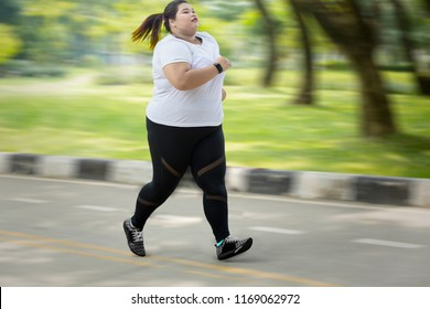 Picture of obese woman wearing sportswear while sprinting on the road with fast motion