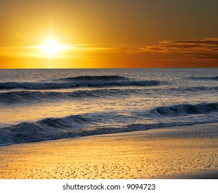a picture of ocean water, sand and sun