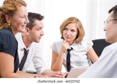 Picture of office workers having meeting in board room Hi Res. Two women and one man discussing certain burning issues concerning business in general and their company in particular.