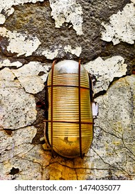 A picture of old damaged concrete wall developing cracks in it with an old rusting grilled light bulb case. A vintage picture depicting damage as time passes and cracks coming there on the wall.
