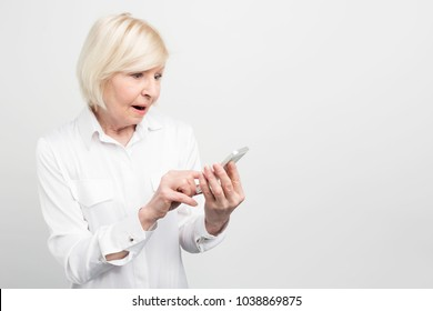 A picture of old lady holding new smartphone. She doesn't know how to use it properly because she didn't have anything like this phone before. Isolated on white background.