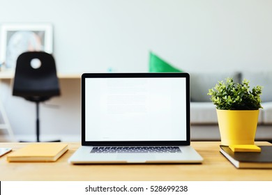 Picture of open laptop on wooden table in living room