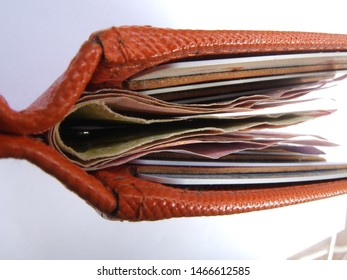 Picture orange wallet. Wallet with money and credit card and ID card on a white background. Wallet money picture.