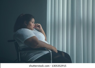 Picture of overweight woman looks sad while sitting in the wheelchair by the window