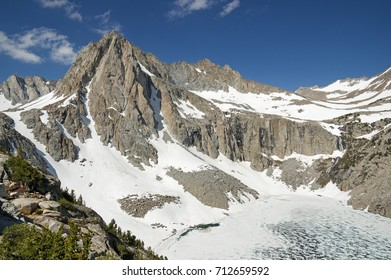 Picture Peak Mountain rises above a still mostly frozen Hungry Packer Lake in the Sierra Nevada Mountains of California