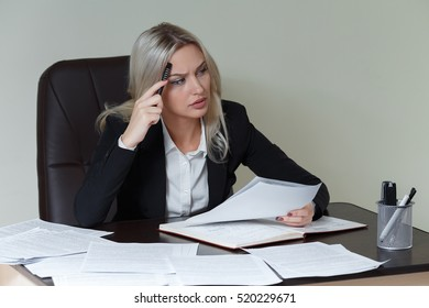 picture of pensive businesswoman with big notepad in suit sitting at the table with documents