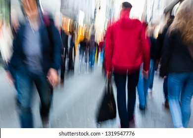 picture of people walking on a shopping street in the city, with camera made motion blur effect