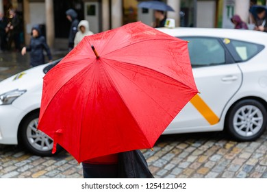 picture of a person with red rain umbrella who crosses a city street