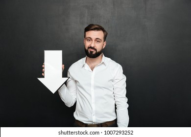 Picture of pessimistic upset man 30s holding blank speech arrow pointer directing downward over dark gray wall copy space