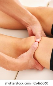 A picture of a physio therapist giving knee massage over white background