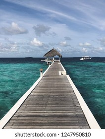 A picture of pier in the maledives. A lot of aqua colours. It's a resort in paradise on a tropical island