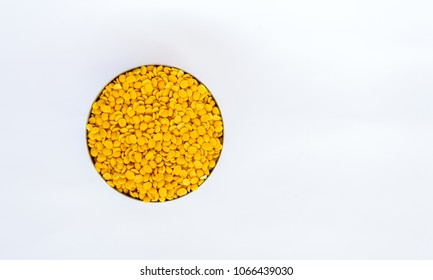Picture of pigeon pea also known as toor dal in a metal bowl. Isolated on white background.