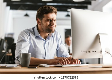 Picture of Playful business man using computer while sitting by the table in office