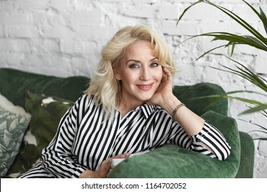 Picture of positive attractive middle aged female wearing natural make up and elegant clothes relaxing at home alone, enjoying free leisure time, looking at camera with happy cheerful smile
