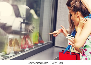 Picture presenting group of girlfriends shopping for shoes in the city with credit card