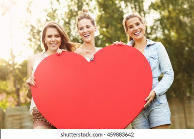 Picture presenting group of women holding big heart outside