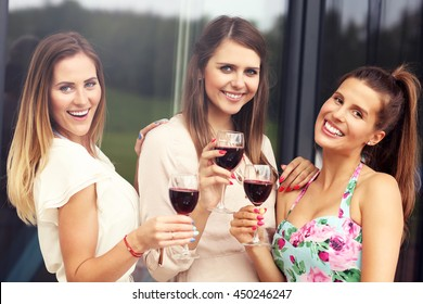 Picture presenting happy group of friends with red wine