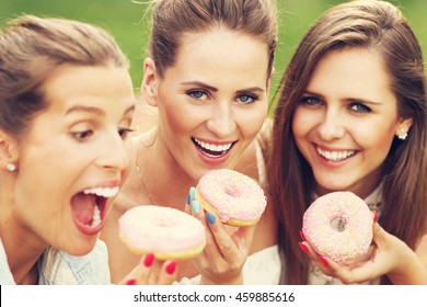 Picture presenting happy group of friends eating donuts outdoors