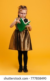 Picture of pretty girl child wearing princess crown standing isolated over yellow background. Looking aside reading book.