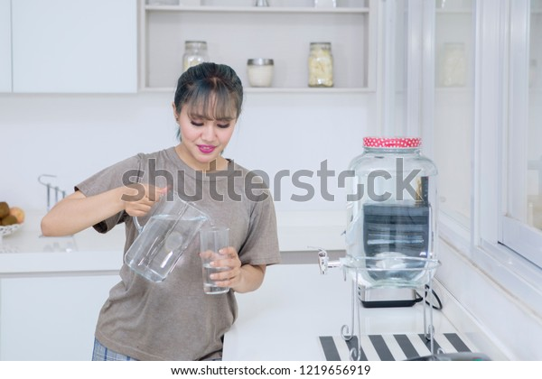 Picture of pretty girl pouring fresh water into the glass while standing in the kitchen room
